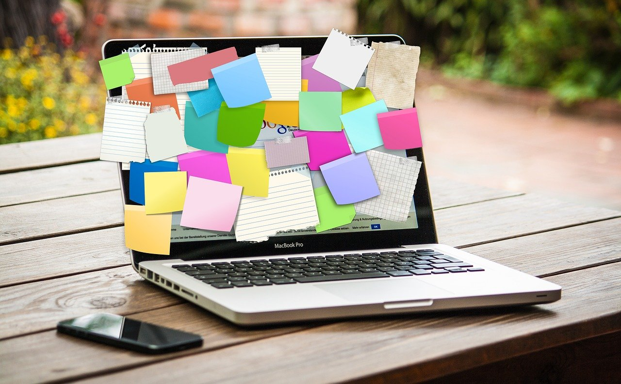 A laptop covered in post-it notes and papers, illustrating that you should organize with a content calendar
