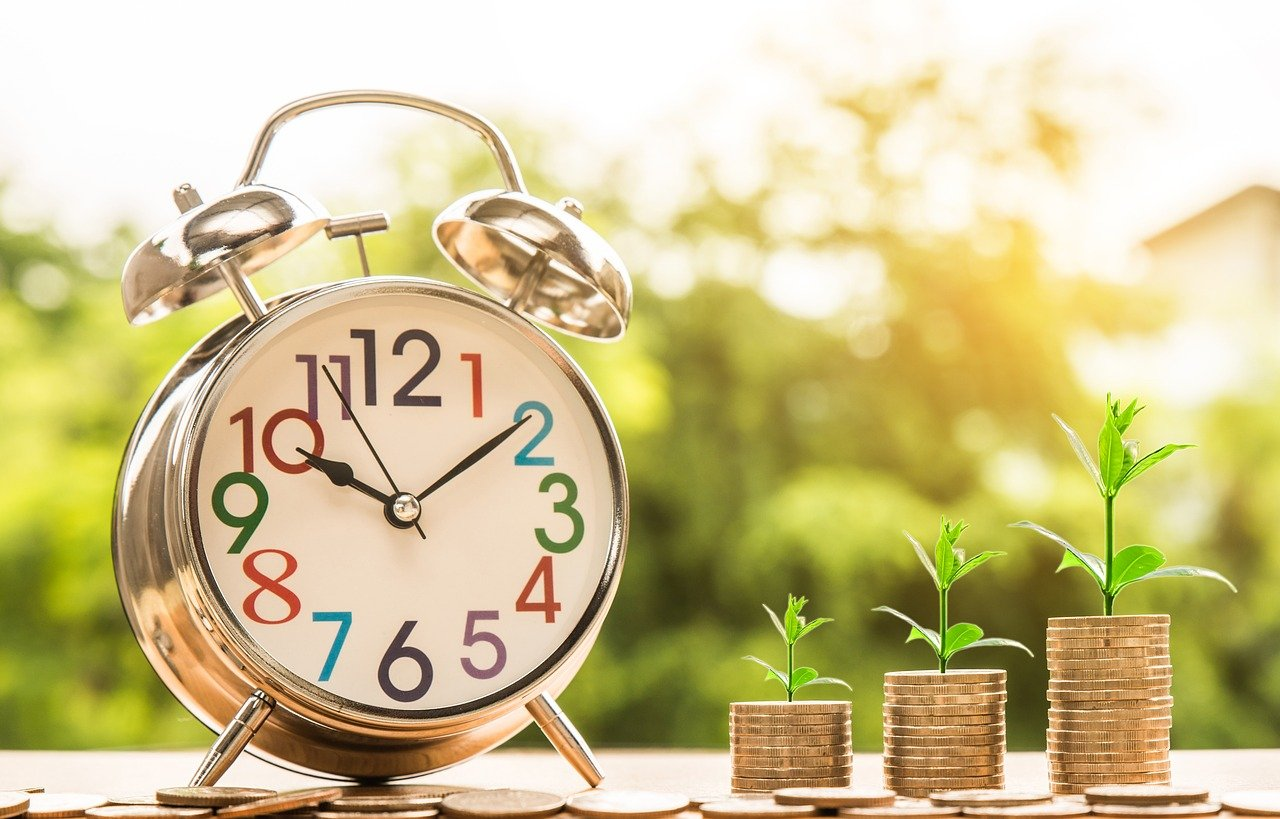 an alarm clock and some coins showing that when you write a free article, you're not earning money for your time